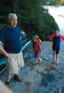 Dad and Lilly and Grace on the rock lakefront Dickie Lake